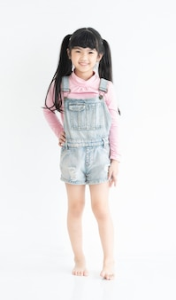Pełna długość szczęśliwej i zabawnej twarzy azjatyckiej sukienki dziewczynki małego dziecka w swobodnej pozycji w białym pokoju.