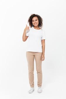 Pełna długość szczęśliwej młodej afrykańskiej kobiety noszącej zwykłe ubrania odizolowane na białej ścianie, kciuk w górę