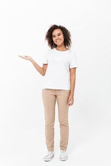 Pełna długość szczęśliwej młodej afrykańskiej kobiety noszącej zwykłe ubrania odizolowane na białej ścianie, prezentującej miejsce na kopię