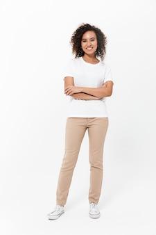 Pełna długość szczęśliwej młodej afrykańskiej kobiety noszącej zwykłe ubrania odizolowane na białej ścianie, z założonymi rękami