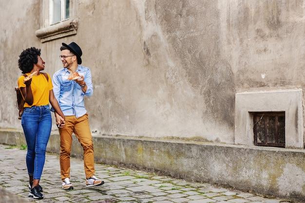 Pełna długość szczęśliwej pary wielorasowej spacerującej na świeżym powietrzu, trzymającej się za ręce i jedzącej pizzę.