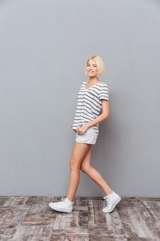 Pełna Długość Szczęśliwej, Uroczej Młodej Kobiety Chodzącej Po Szarej ścianie Premium Zdjęcia