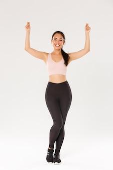 Pełna długość treningu szczupłej i zdrowej uśmiechniętej azjatyckiej dziewczyny, stojącej w odzieży sportowej i podnoszącej ręce do góry, jakby trzymała znak lub baner, reklamuj sprzęt sportowy lub zniżki na członkostwo w siłowni.