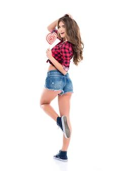 Pełna długość uroczej, szczęśliwej młodej kobiety w kraciastej koszuli i dżinsowych szortach pozujących z cukierkiem w kształcie serca na białej ścianie