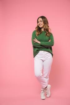 Pełna długość uśmiechnięta blondynka ubrana w zielony sweter pozuje ze skrzyżowanymi rękami i odwraca wzrok na różowej ścianie