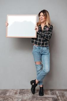 Pełna długość uśmiechnięta kobieta trzyma puste miejsce deskę