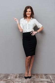 Pełna długość uśmiechnięta kobieta w biznesie odziewa pozować i wskazuje daleko od na szarość