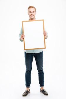 Pełna długość uśmiechniętego młodego mężczyzny trzymającego pustą tablicę nad białą ścianą