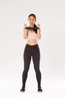 Pełna długość uśmiechniętej i zdeterminowanej, szczupłej brunetki azjatyckiej fitness dziewczyny, trener treningowy pokazujący ćwiczenia z rozciąganiem oporu, demonstruje sprzęt do ćwiczeń.
