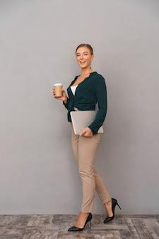 Pełna długość uśmiechniętej młodej bizneswoman
