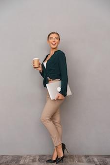 Pełna długość uśmiechniętej młodej bizneswomanu stojącego