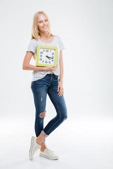 Pełna długość uśmiechniętej pięknej młodej kobiety stojącej i trzymającej zegar na białej ścianie