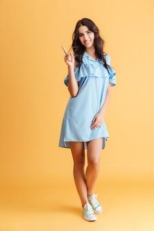 Pełna długość uśmiechniętej, szczęśliwej kobiety w niebieskiej sukience, wskazując palcem w górę