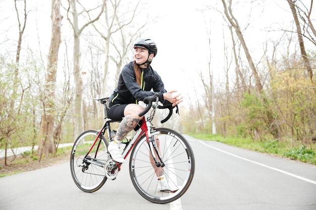 Pełna długość uśmiechniętej, wytatuowanej młodej kobiety w kasku rowerowym na rowerze stojącym na drodze w parku