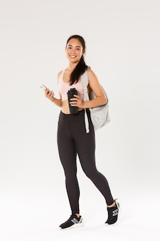 Pełna długość uśmiechniętej zdrowej, szczupłej azjatki idącej na trening fitness, athelte niosąca plecak ze sprzętem do ćwiczeń i butelką wody, przy użyciu telefonu komórkowego, białe tło.