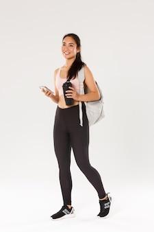 Pełna długość uśmiechniętej zdrowej, szczupłej azjatyckiej dziewczyny idącej na trening fitness, sportowego plecaka ze sprzętem do ćwiczeń i butelką wody, korzystającej z aplikacji sportowej na telefon komórkowy, biała ściana