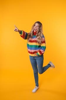 Pełna długość wesoła blondynka w kolorowym swetrze wskazującym palcem na bok na copyspace odizolowanej nad żółtą ścianą