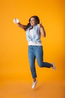 Pełna długość wesoła młoda kobieta skacząca na białym tle, robiąc selfie z wyciągniętą ręką