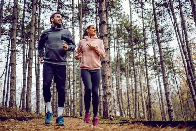 Pełna długość wesoła młoda para w odzieży sportowej biegającej w przyrodzie.