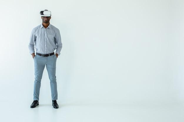 Pełna długość wesołego afroamerykańskiego mężczyzny w okularach vr i uśmiechającego się na białej ścianie
