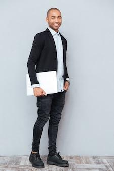 Pełna długość wesołego afroamerykańskiego młodego biznesmena z laptopem