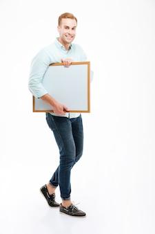 Pełna długość wesołego afrykańskiego młodego człowieka chodzącego i trzymającego tablicę