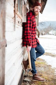 Pełna długość wesołego brodatego młodego mężczyzny z siekierą stojącego w pobliżu starego drewnianego domu we wsi