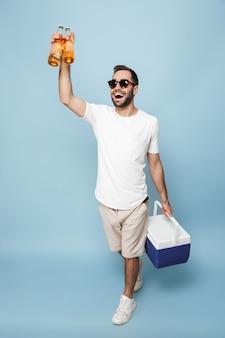Pełna długość wesołego podekscytowanego mężczyzny w pustej koszulce stojącego na białym tle nad niebieską ścianą, niosącego chłodziarkę z zimnym piwem