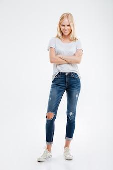 Pełna długość wesołej ładnej młodej kobiety stojącej z rękami skrzyżowanymi na białej ścianie