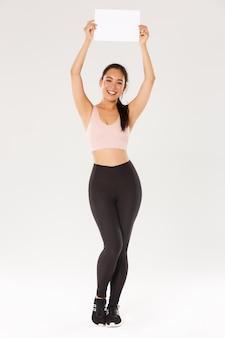 Pełna długość wesołej, szczupłej i wesołej uroczej dziewczyny trenującej na siłowni, stojącej w ubraniu sportowym i podnoszącej znak, pusta kartka papieru z twoją reklamą, stojąca na białym tle.
