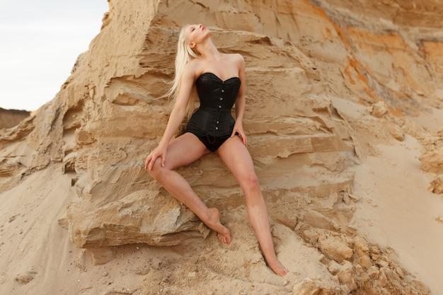 Pełna długość widok zmysłowej młodej kobiety z długimi blond włosami nosić w czarnym gorsecie, patrząc z postawą na aparat, tło klify piasku.