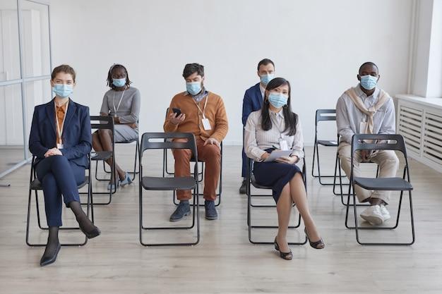 Pełna długość wieloetniczna grupa ludzi biznesu noszących maski i dystansujących się, siedząc na krzesłach na widowni podczas konferencji biznesowej lub seminarium