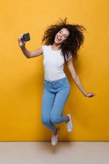 Pełna długość wspaniałej kobiety w wieku 20 lat z kręconymi włosami, trzymającej smartfona i robiącej zdjęcie selfie izolowane na żółto