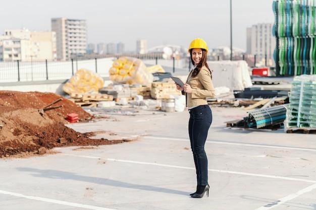 Pełna długość wspaniały żeński architekt z brown włosy, ubierający mądrze przypadkowym i hełmem na kierowniczej mienie pastylce podczas gdy stojący przy budową.