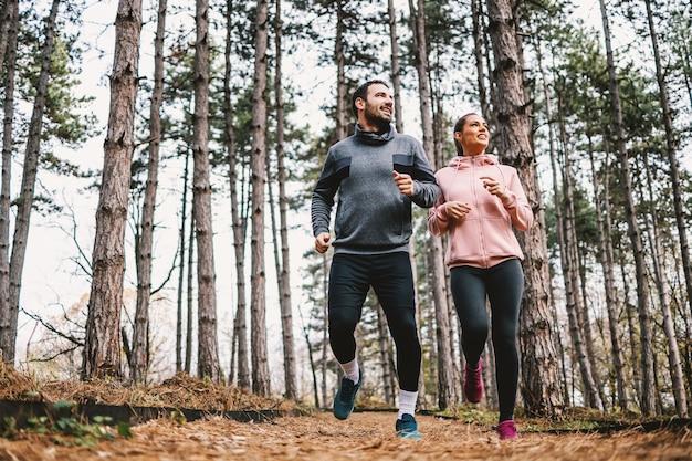 Pełna długość wysportowanej pary biegnącej jesienią po lesie i przygotowującej się do maratonu.