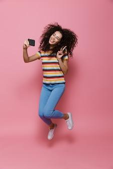 Pełna długość zabawnej kobiety w wieku 20 lat z kręconymi włosami, trzymającej smartfona i robiącej zdjęcie selfie odizolowane na różowo