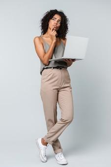 Pełna długość zamyślona młoda afrykańska kobieta ubrana niedbale stojących na białym tle, pracująca na komputerze przenośnym