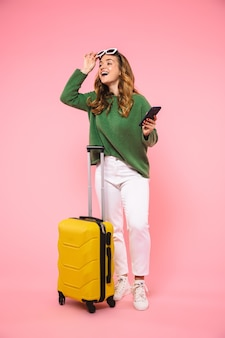 Pełna długość zaskoczona szczęśliwa blondynka ubrana w zielony sweter zdejmuje okulary przeciwsłoneczne i odwraca wzrok, trzymając smartfona i pozując z bagażem na różowej ścianie