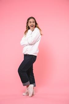 Pełna długość zaskoczona szczęśliwa blondynka ubrana w zwykłe ubrania raduje się i patrzy na przód ponad różową ścianą