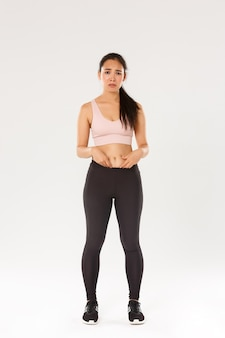 Pełna długość zdenerwowanej i ponurej azjatki w stroju fitness, pokazująca tłuszcz na brzuchu, narzekająca na ciało, marszcząca brwi i rozczarowana, rozpoczynająca trening, próbująca schudnąć, białe tło.