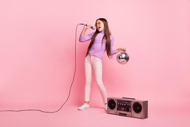 Pełna długość zdjęcia fajnej małej dziewczynki śpiewającej piosenkę z mikrofonem, trzymając piłkę dyskotekową z boom boxem na białym tle nad pastelowym kolorem tła