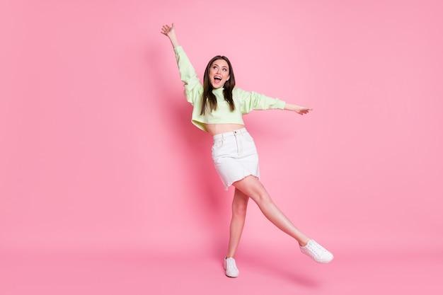Pełna długość zdjęcie atrakcyjnego młodzieńca pani podnosić ramiona nogi wysoki taniec studentów party dobry nastrój nosić casual crop sweter nagi brzuch dżinsy spódnica buty na białym tle różowy kolor tła