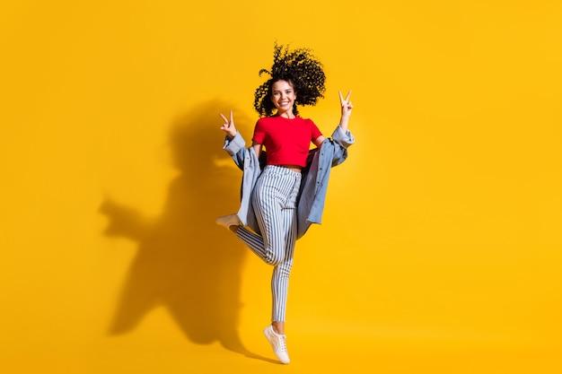 Pełna długość zdjęcie dziewczyny pobyt na palcach pokaż znak v nosić paski dżinsy przycięte czerwona koszulka kurtka trampki na białym tle żółty kolor tła