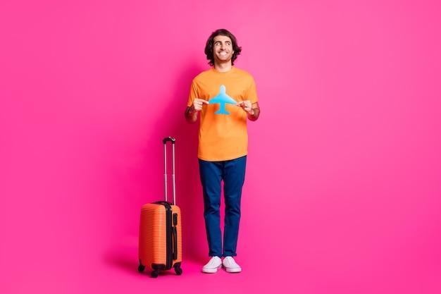 Pełna długość zdjęcie faceta torba trzyma papierowy samolot wygląda na pustą przestrzeń nosić pomarańczowy t-shirt dżinsy trampki na białym tle różowy kolor