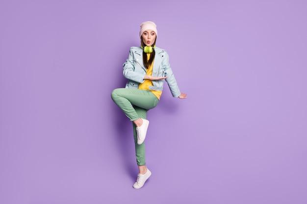 Pełna długość zdjęcie funky atrakcyjna dama stylowe ubrania dobry nastrój taniec młodzieniec porusza się podnieście ręce nogę radośnie nosić dorywczo kapelusz kurtka spodnie buty na białym tle fioletowy kolor tła