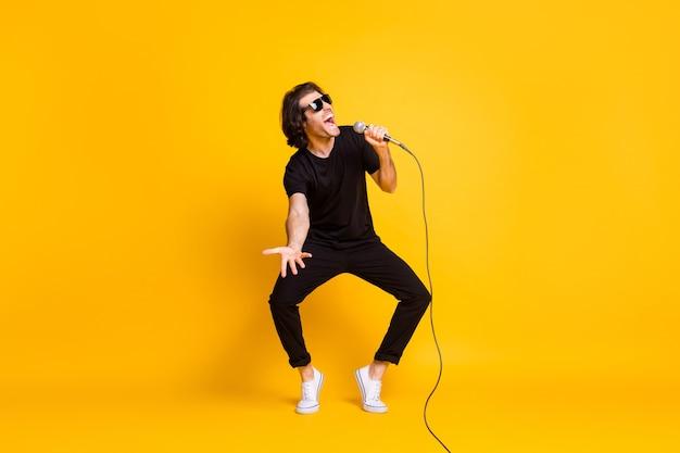 Pełna długość zdjęcie młodego człowieka taniec trzymać mikrofon śpiewać otwarte usta nosić czarny t-shirt spodnie białe trampki okulary na białym tle żółty kolor tła