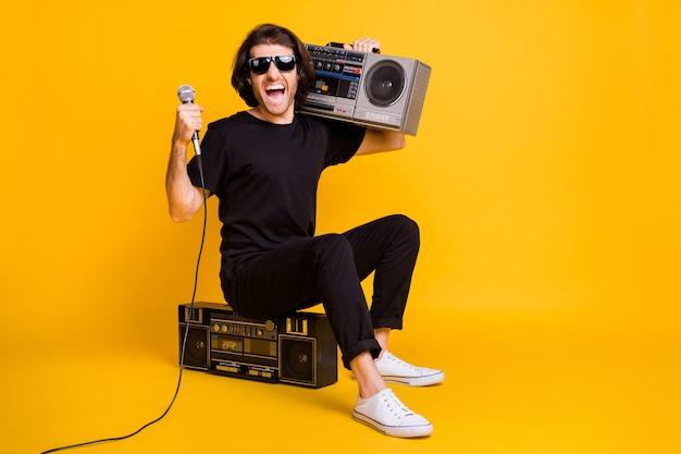 Pełna długość zdjęcie młodego człowieka trzymać mikrofon otwarte usta ramię boombox siedzieć nosić czarny t-shirt spodnie białe trampki okulary na białym tle żółty kolor tła