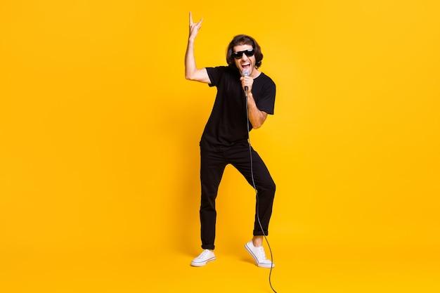 Pełna długość zdjęcie młodego człowieka trzymać mikrofon śpiewać otwarte usta pokaż rogi nosić czarny t-shirt spodnie białe trampki okulary na białym tle żółty kolor tła