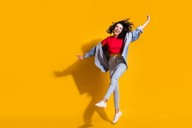 Pełna długość zdjęcie pani skok podniesione nogi ręce nosić paski dżinsy przycięte czerwone t-shirt kurtka trampki na białym tle żółty kolor tła