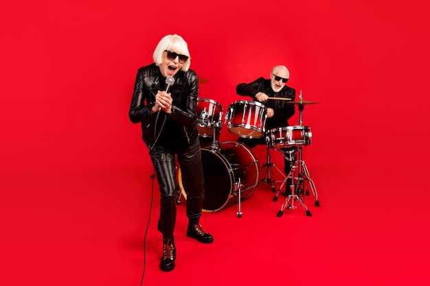 Pełna długość zdjęcie siwych białych włosów dwie osoby emeryt żona mąż zespół rockowy człowiek grać bęben kobieta śpiewać solo kompozycja mikrofon cieszyć studio dźwięk wydarzenie na białym tle jasny kolor tła